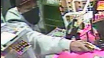 IMPD released this image from a security camera showing a robber with a pistol Wednesday night at a gas station at 5220 W. Troy Ave.