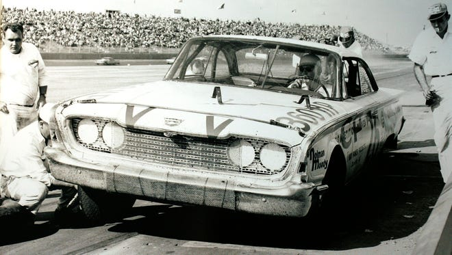 Curtis Turner pits during the first World 600. A window screen has been placed across the front of his Holman-Moody Ford to prevent pieces of the track from hitting the grille and radiator.