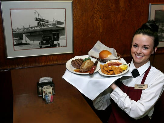Server Amanda Jackson holds a tray with a beef filet, baked potato and lamb fries at the Cattlemen's Steakhouse restaurant in Oklahoma City. The restaurant, which first opened in 1910 as the Cattlemen's Cafe, is known for quality beef.
