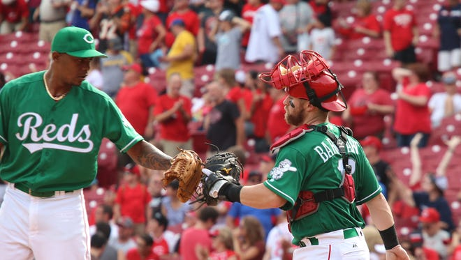 Reds catcher Tucker Barnhart (right) is congratulated by pitcher Raisel Iglesias after defeating the Pittsburgh Pirates on Sunday.