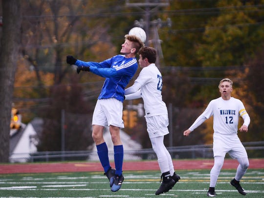Garrett Mironenko (no. 22) of Waldwick (in white)goes head to head against Damian Zurawski (no. 22) of Wallington (in blue) in the first half during the North 1, Group 1 state semifinal at Waldwick High School on 11/07/17.