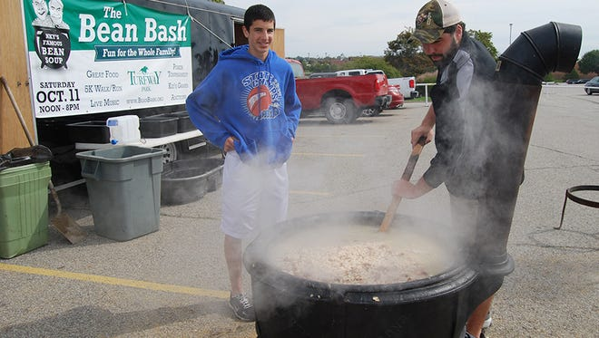From left, volunteers, Casey Nowalk, a student of Covington Catholic, and his brother Connor, a student at Eastern Kentucky University from Burlington, stir the beans for the Bean Bash held Saturday, Oct. 11, at Turfway Park.
