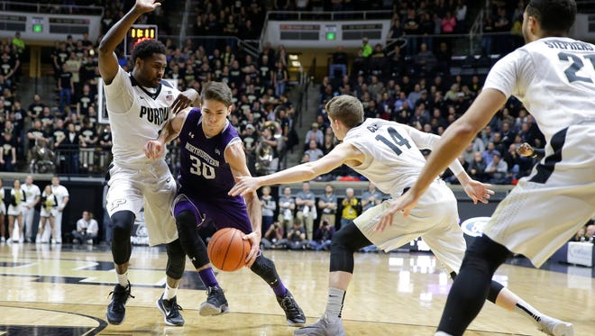 Northwestern guard Bryant McIntosh (30) drives between Purdue guard Johnny Hill (1) and guard Ryan Cline (14) in the first half of an NCAA college basketball game in West Lafayette, Ind., Tuesday, Feb. 16, 2016. (AP Photo/Michael Conroy)