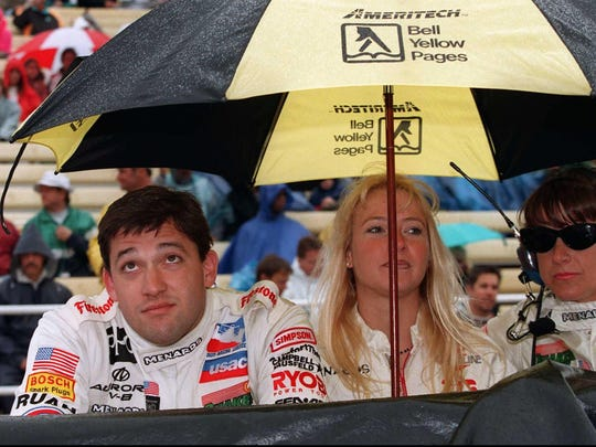 Driver Tony Stewart, left, Krista Dwyer, center, and Bobbi Marra wait under an umbrella in the pits during a rain delay at the Indianapolis Motor Speedway, Monday, May 26, 1997. Stewart was leading the field of the Indy 500 when rain stopped the race after 15 laps were completed.