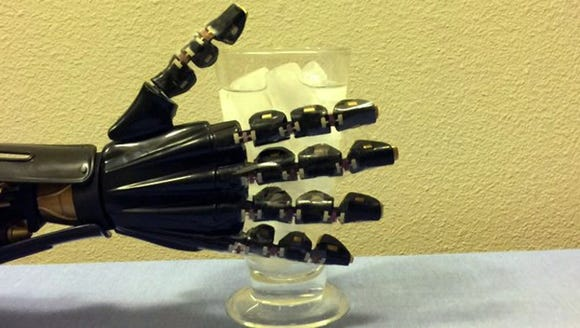 A robot hand with artificial skin reaches for a glass