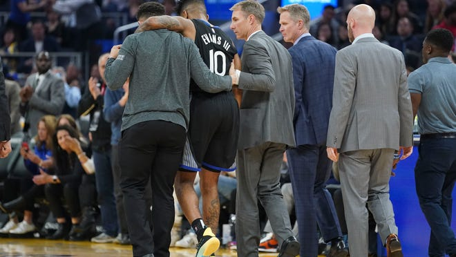 January 14, 2020; San Francisco, California, USA; Golden State Warriors guard Jacob Evans (10) is helped off the court after an injury against the Dallas Mavericks during the second quarter at Chase Center. Mandatory Credit: Kyle Terada-USA TODAY Sports