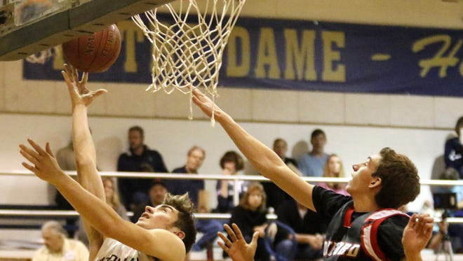 Gary Raupers goes up for a layup as Jason Davis tries to block the shot Tuesday at Notre Dame High School.