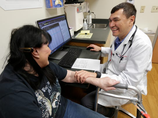 Dr. Moises Garcia talks with one of his longtime patients,