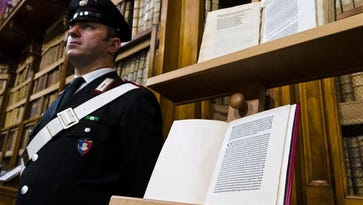 A policeman stands next to a book, containing a letter written by Christopher Columbus, in Rome.