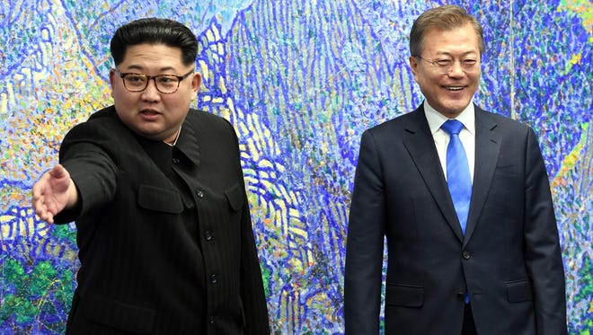 North Korea's leader Kim Jong Un (left) gestures next to South Korea's President Moon Jae-in (right) as they pose for a photo during the Inter-Korean summit in the Peace House building on the southern side of the truce village of Panmunjom.
