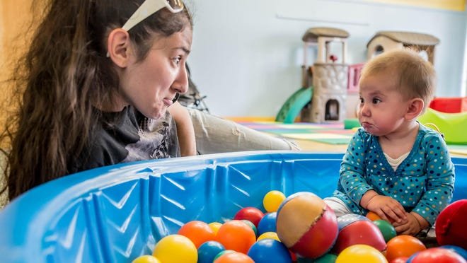 Six-month-old Ellia Gillern and her mom Mariah from Albion looks at her daughter sit in a pool of colored balls at Kids 'N' Stuff in downtown Albion.