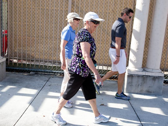 Pat Hohman, left, Elinor Hughes, center, and Lee Memorial Health Service Representative Blain Lindsey, right, chat as they walk through Coconut Point mall on National Walking Day Wednesday April 6, 2016, at Coconut Point mall in Estero.