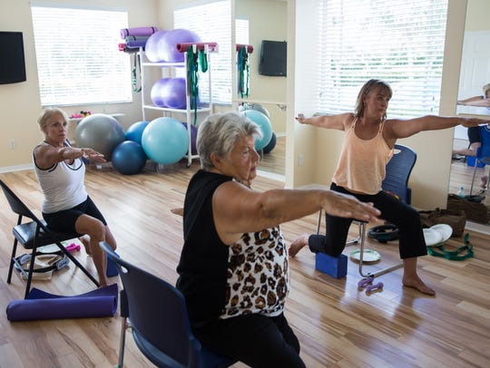 Yoga instructor Elaine Malone, right, leads a class