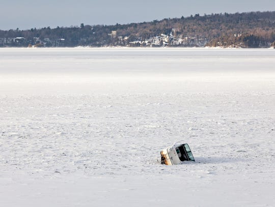 A boat lies frozen in the ice on Malletts Bay in Colchester