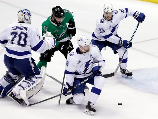 Tampa Bay Lightning goalie Louis Domingue (70) watches from beyond the net as defenseman Anton Stralman (6), of Sweden, and center Brayden Point (21) help clear a puck under pressure from Dallas Stars center Tyler Seguin (91) in overtime of an NHL hockey game Thursday, March 1, 2018, in Dallas. (AP Photo/Tony Gutierrez)
