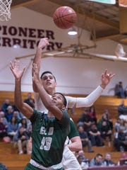 El Diamante's Jayvon Hightower and Mt. Whitney's Anthony Valencia go up for a rebound in a West Yosemite League high school boys basketball game on Wednesday, January 3, 2018.