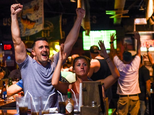 Scott Meyer jumps from his chair in celebration as the Philadelphia Eagles scores against the New England Patriots during Super Bowl 52 gameplay viewed at the Horse & Cow Pub & Grill in Tamuning on Monday, Feb. 5, 2018.
