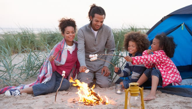 Family Camping On Beach And Toasting Marshmallows Over Fire