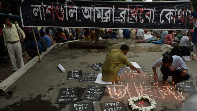 Indian social activists light candles during a protest in Kolkata on July 2 against a fatal attack on a restaurant in the Bangladeshi capital Dhaka.