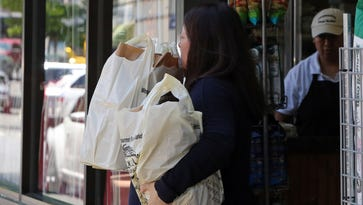 A shopper leaves Chappaqua Village Market with groceries June 2, 2016 in Chappaqua. Starting Jan. 1, 2017, a new law in New Castle will prohibit single-use plastic shopping bags in various stores in order to encourage the use of reusable shopping bags.