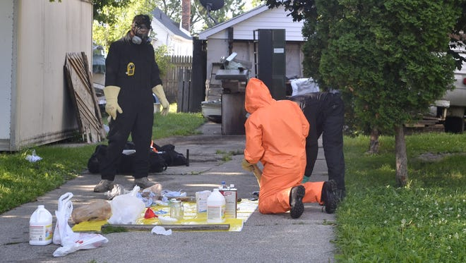 MARK R. RUMMEL/ TIMES HERALD St. Clair County Drug Task Force and Port Huron Police go through items from a suspected meth lab Friday morning in Port Huron. St. Clair County Drug Task Force and Port Huron Police go through items from a suspected meth lab Friday morning, July 24 on Varney in Port Huron.