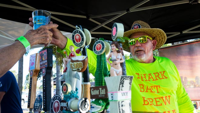 Robbie Toombs of Miami Brewing Co. provides a sample of craft beer during Bonita Brew Fest at Riverside Park in Bonita Springs, Florida on Saturday, Feb. 4. Festival goers enjoyed unlimited 3 oz. samples of some of the best craft brews from Florida and beyond.