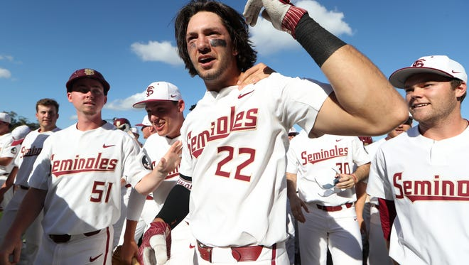 FSU's Drew Mendoza is mobbed by his teammates after hitting a walk-off single against Troy as the Seminoles stay undefeated on the year with the 6-5 win at Dick Howser Stadium on Saturday, Feb. 24, 2018.