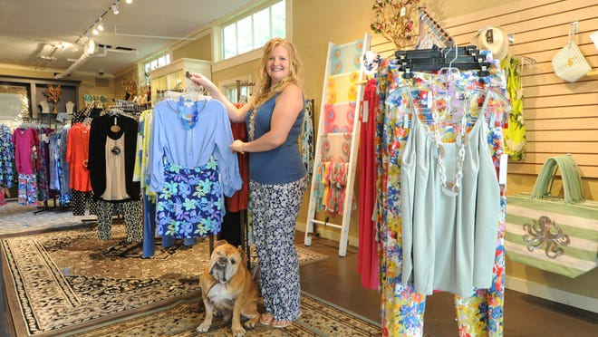 SeaSide Boutique owner Heather Miller, with her dog, Georgie, has reopened her Sandwich shop under new safety guidelines. Retail stores were allowed to open earlier this week as part of the state's second phase of reopening.