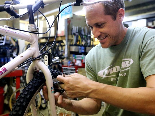 MOAB owner Mark Dement works on a bike in his shop on Friday, August 22, 2014.
