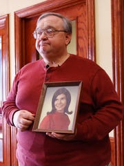 Bob Look holds a portrait of his wife, Dianne Renaud-Look,