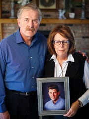 Mark and Denise Kuhn hold a portrait of their son Alex in their home near Charles City Monday, Feb. 13, 2017.