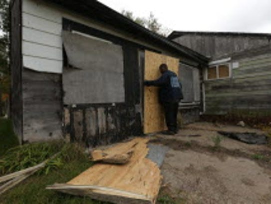 Lory Welch boards up an abandoned home in the 1800
