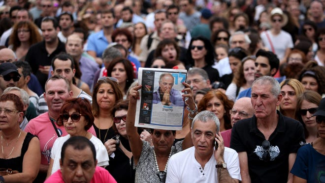 An Israeli woman holds of portrait of late Israeli singer-songwriter Arik Einstein during his funeral ceremony in Tel Aviv, on Nov. 27. His death brought Israel to a virtual standstill.
