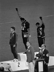 """Tommie Smith (center) and John Carlos stare downward during the playing of """"The Star Spangled Banner"""" after Smith received the gold and Carlos the bronze for the 200 meter run at the Summer Olympic Games in 1968. Australian silver medalist Peter Norman is at left. Carlos, one third of the iconic image, spoke at Rutgers-Camden Wednesday."""