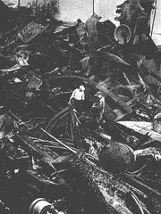 Two men look over the twisted machinery and charred timbers left from the July 8, 1968, fire at the Capitol Lumber Company.