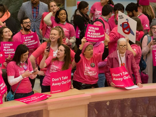 Advocates for Planned Parenthood rally after Gov. Scott
