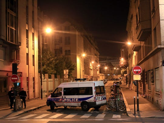 Police officers stand in a street next to Le Carillon,
