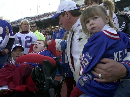 Jim Kelly, center, looks after his son Hunter, while waiting with his daughter Camryn, right, and wife Jill, left,  before having his number retired at Ralph Wilson stadium in Orchard Park on Nov. 18, 2001.