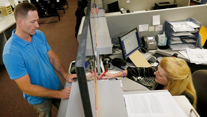 Elmira resident Jim McCabe is assisted by clerk/cashier Terri Brimmer while renewing his license Oct. 22 at the Chemung County Department of Motor Vehicles in Elmira.