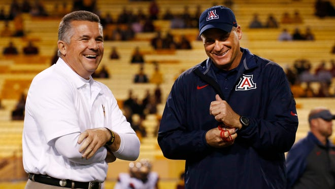 ASU head coach Todd Graham talks to Arizona head coach Rich Rodriguez before kick-off at the 87th Territorial Cup on Saturday, Nov. 30, 2013 in Tempe.