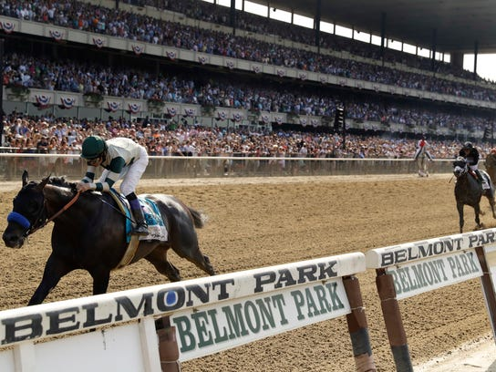Mike Smith crosses the finish line riding Mor Spirit to win the Mohegan Sun Metropolitan, the jockey's fifth win of the day, at Belmont Park, Saturday, June 10, 2017, in Elmont, N.Y. (AP Photo/Julio Cortez)