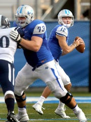 MTSU's quarteback Brent Stockstill (12) drops back to pass as Chandler Brewer keeps Jackson State away from Stockstill during the first half of an NCAA college football game against Jackson State, on Saturday, Sept. 5, 2014, in Murfreesboro, Tenn. (AP Photo/Daily News Journal, Helen Comer)