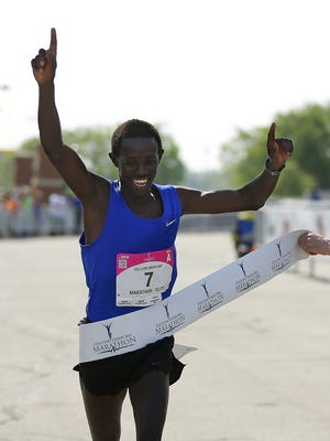 Abraham Rutto, of South Floral Park, N.Y, crosses the finish line to win the men's Cellcom Green Bay Marathon in Green Bay on Sunday, May 22, 2016.