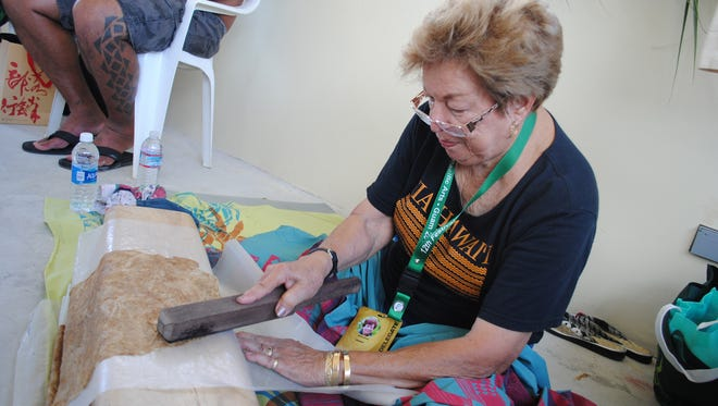 Moana Eisele demonstrates the art of making Kapa, a cloth-like material made from pounding the cambium layer of a tree, at the Festival Village in front of the Paseo Stadium in Hagåtña May 25..