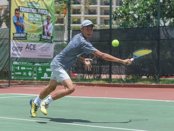 Ming-Chieh Chiu, 16, lunges for the ball during his