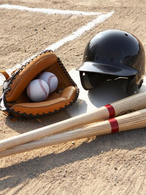 Baseball glove, balls, bats and baseball helmet at home plate.