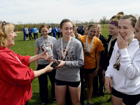 Palmyra's Miranda Salvo accepts the Lebanon County team championship trophy for the Cougars on Saturday as her happy teammates look on.