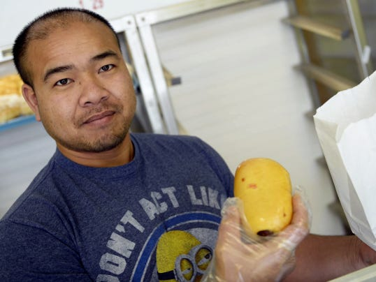 Sabun Khiev, owner of Honeybun Donuts, at 720 Jonestown Road in Lebanon holds up a kolache -- which is a smoked sausage wrapped in a glazed doughnut --  on Tuesday, January 6, 2015. Jeremy Long -- Lebanon daily News