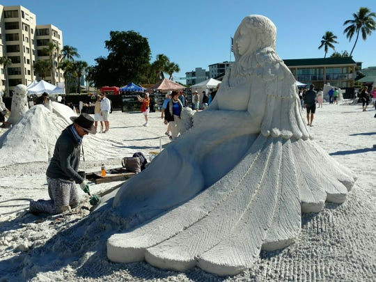 Remy Hoggard, of the Netherlands and Bulgaria, sculpts a woman holding an owl during the American Sand Sculpting Championship at Fort Myers Beach. On the back side, an owl and its feathers create the woman's cape.