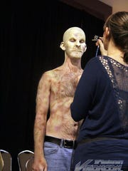 A convention attendee gets makeup applied at Visioncon 2016.